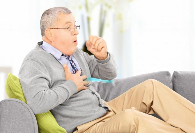 man-coughing-on-gray-couch_670x505
